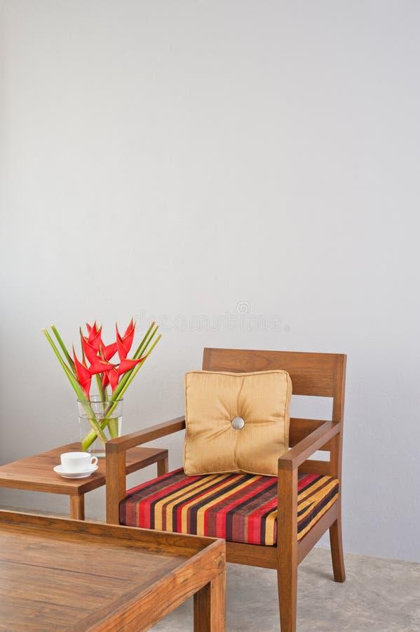 Beiga stoppad stol med sidotabellen och blommor arkivfoto