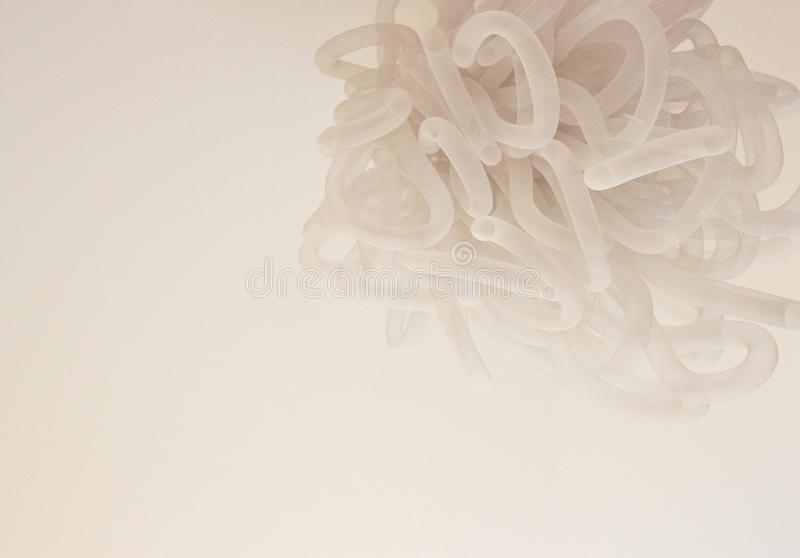 Beige abstract chandelier made of spiral wrapped soft lines stock image