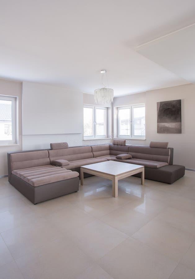 Beige angular sofa. In luxury drawing room royalty free stock image