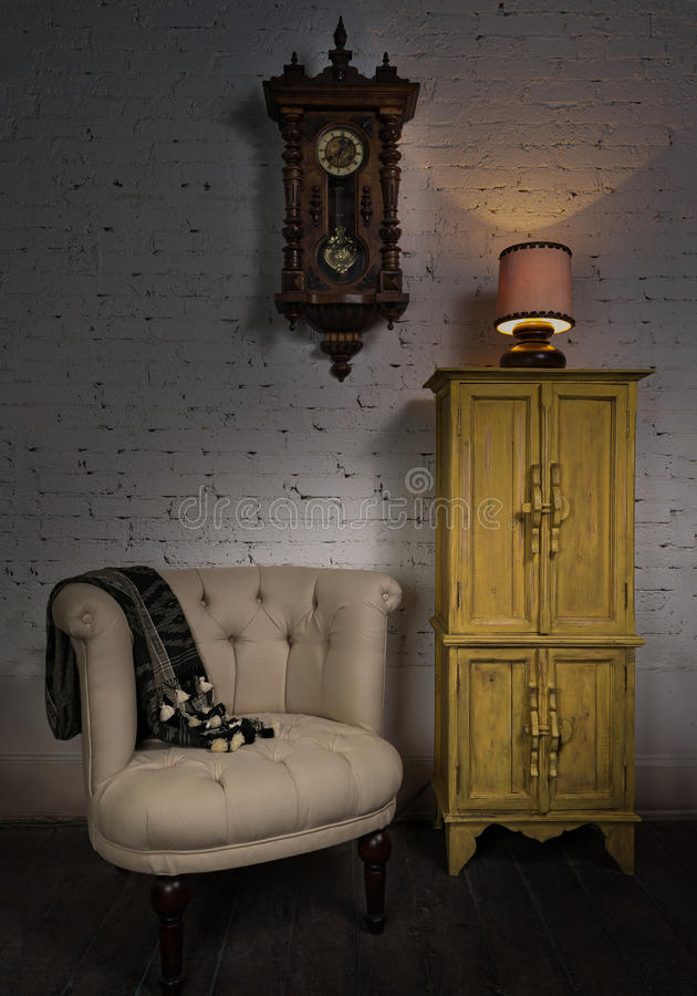 Beige armchair, yellow cupboard, pendulum clock and illuminated table lamp stock image