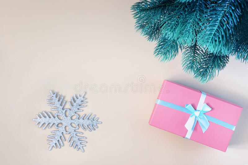 On a beige background a gift in a pink box, fir branch and a decorative snowflake. A place for inscriptions and texts stock image