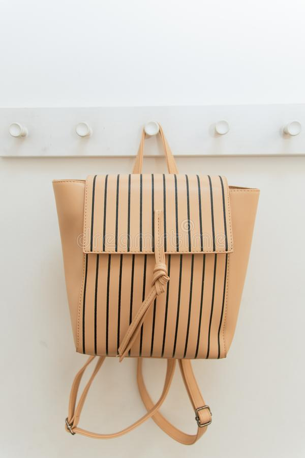 Beige backpack on a hanger in the closet. A backpack hangs on a hook in a shop fitting room. stock photo