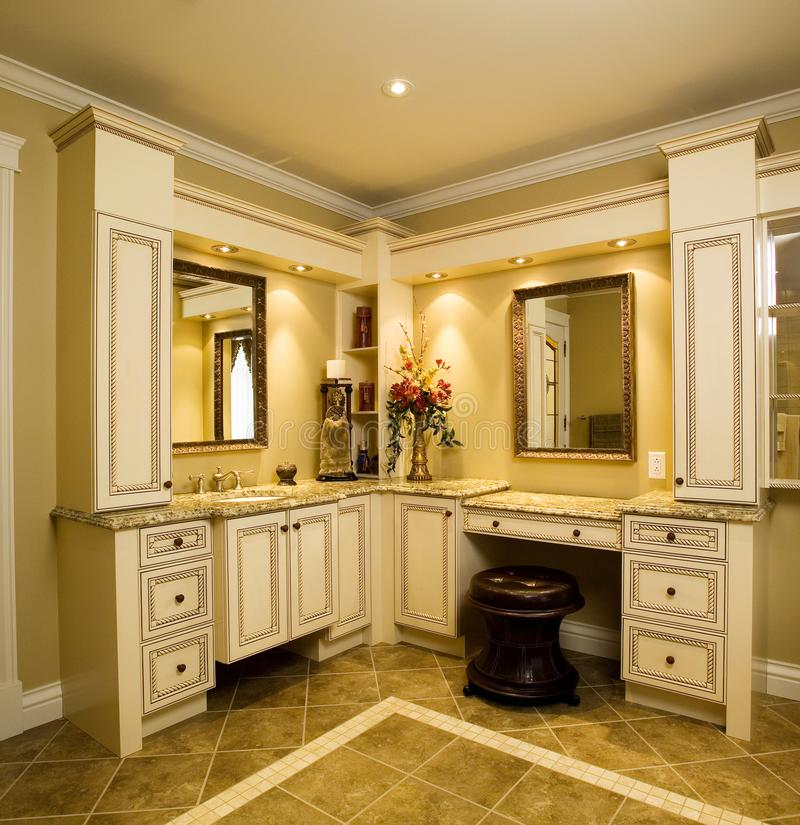 Beige bathroom cabinets with granite counter top royalty free stock photos