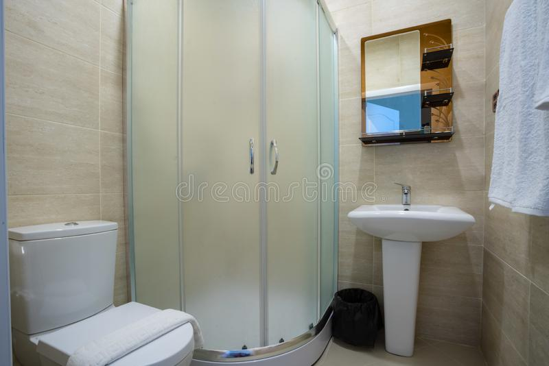 Beige bathroom with glazed shower, mirror over the sink, towel and toilet. stock photography