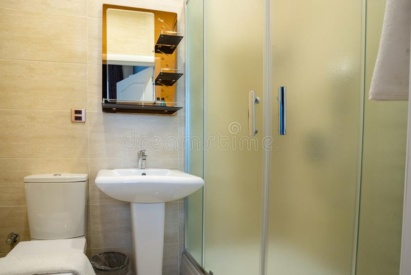 Beige bathroom with glazed shower, mirror over the sink, towel and toilet. stock photo
