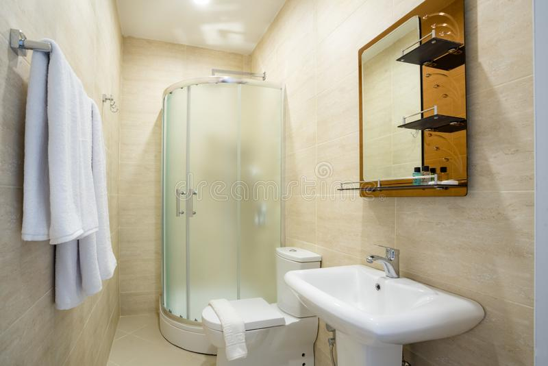 Beige bathroom with glazed shower, mirror over the sink, towel and toilet. stock images