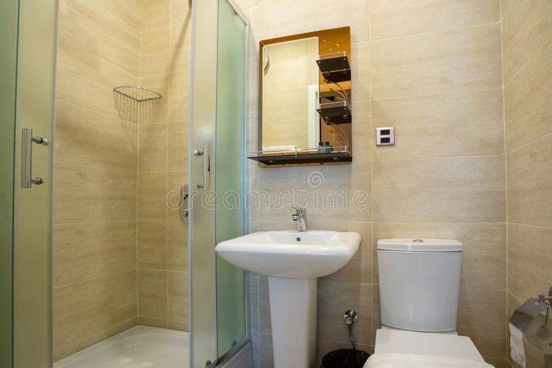 Beige bathroom with glazed shower, mirror over the sink, towel and toilet. royalty free stock photos