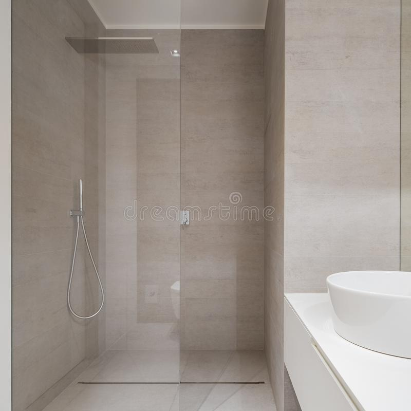 Simple beige bathroom with shower. Simple and elegant beige bathroom with modern shower and countertop basin stock image