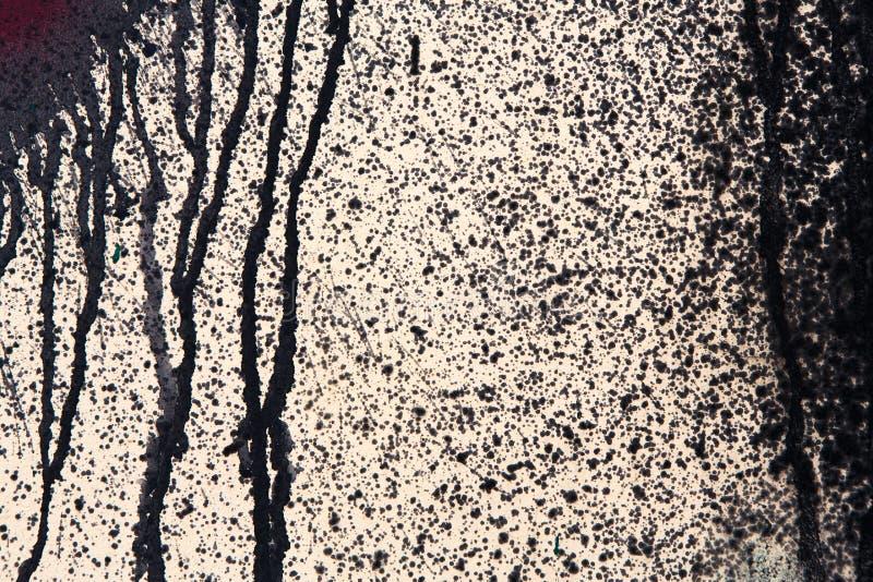 Beige betongvägg med svarta målarfärgdroppander, abstrakt bakgrund royaltyfria bilder