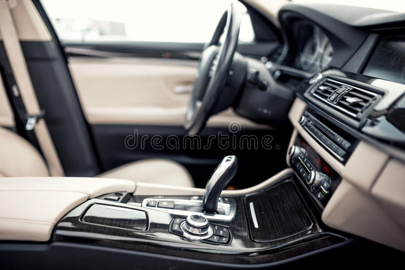 Beige and black interior of modern car, close-up details of automatic transmission and gear stick against steering wheel ba stock photo