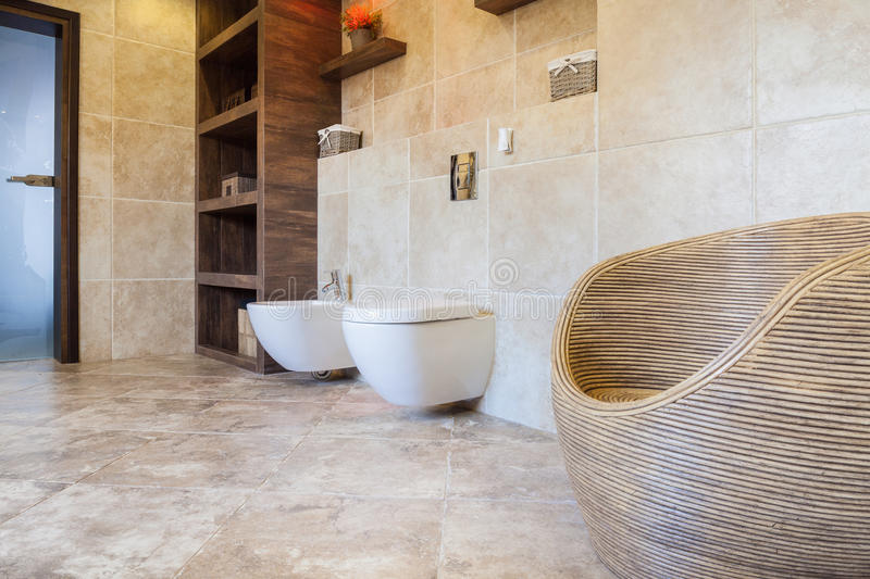 Beige and bright bathroom. With wicker chair stock image