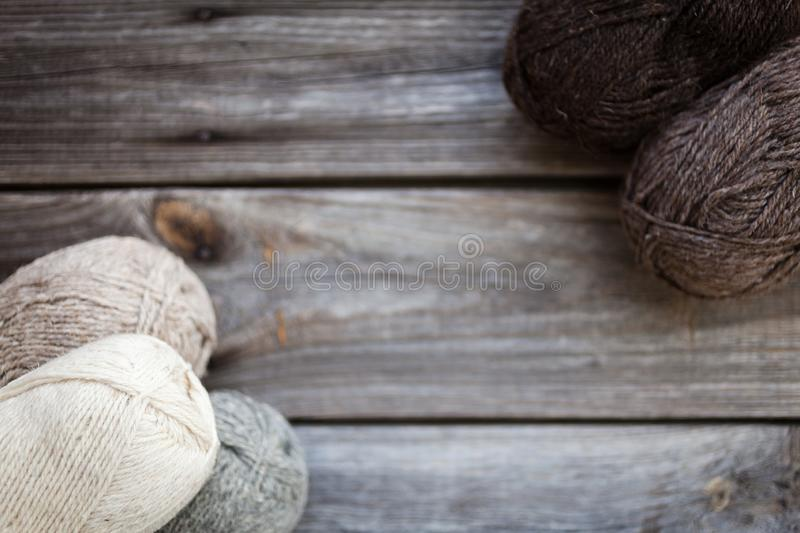 Beige, brown, gray and white balls of yarn. Wooden background royalty free stock images