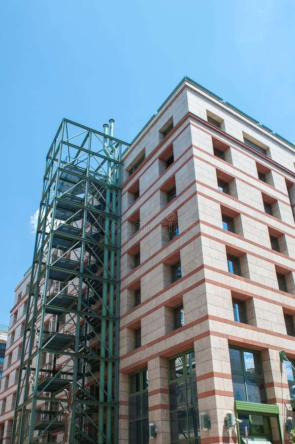 Beige byggnad med den gröna trappuppgången, fönster som beläggas med tegel royaltyfri foto