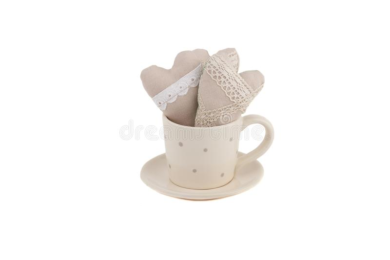 Beige ceramic cup for coffee or tea with decorative hearts inside. White background royalty free stock photo
