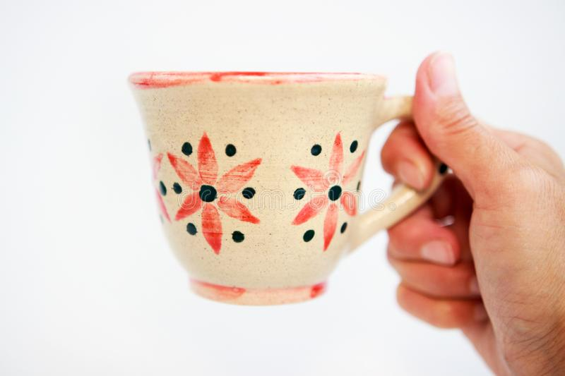 Beige clay cup with flowers in hand on a white background royalty free stock photography