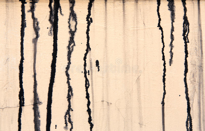 Beige concrete wall with black paint drips, abstract background royalty free stock photography