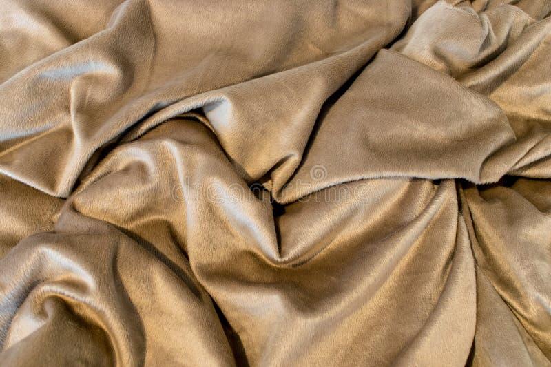 Beige Decke mit gelegentlichen Deepsfalten stockfoto