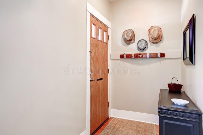 Beige Eingang mit Kabinett, Spiegel, Hüte, die an der Wand hängen lizenzfreie stockbilder