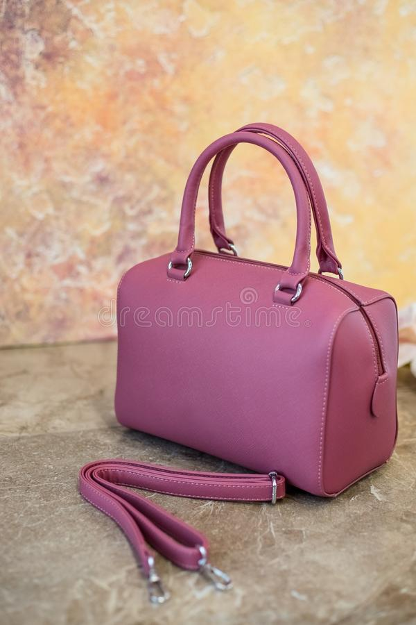 Purple elegant leather tote shoulder bag isolated on yellow background.The Leather female handbag.Fashion. Clothes stock photography