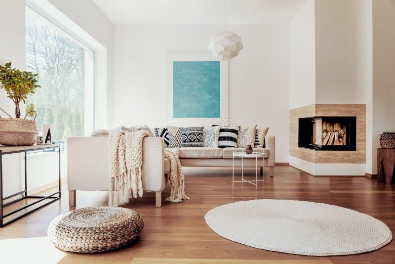 Beige en witte textiel en een modern sferisch tegenhangerlicht in een zonnig, rustig woonkamerbinnenland met natuurlijk decor royalty-vrije stock afbeeldingen