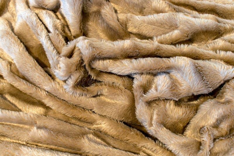 Beige f aux fur many random folds create interesting texture. A beige f aux fur blanket folded in a way to create many random folds and textures stock photos