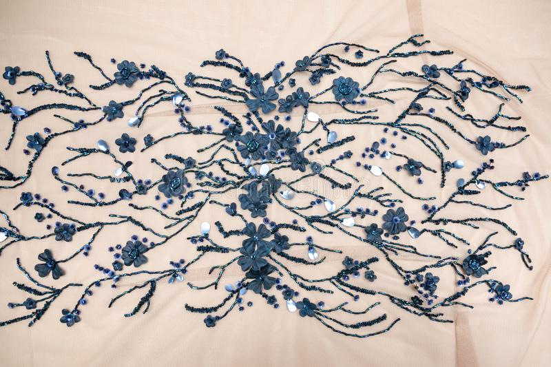Beige fabric with blue beads, with patterns of beads in the form of flowers on the branches spread out on the table. stock image