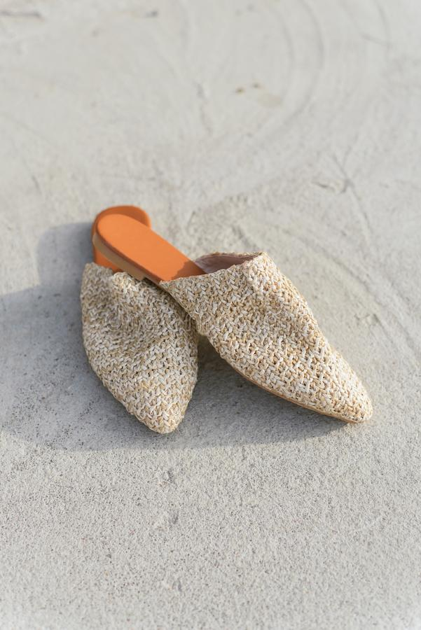 Beige fashion wicker mules on the background of asphalt and concrete. stylish, summer and trend shoes stock image