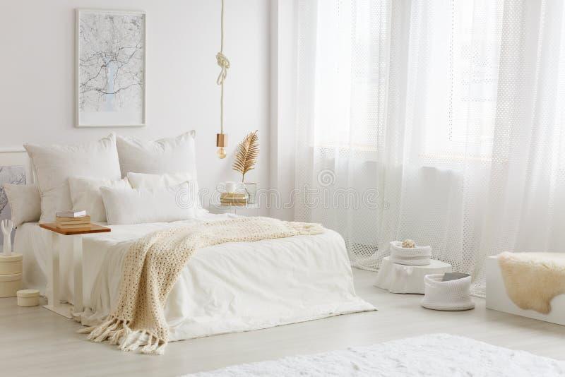 Beige filt på vit säng arkivbild