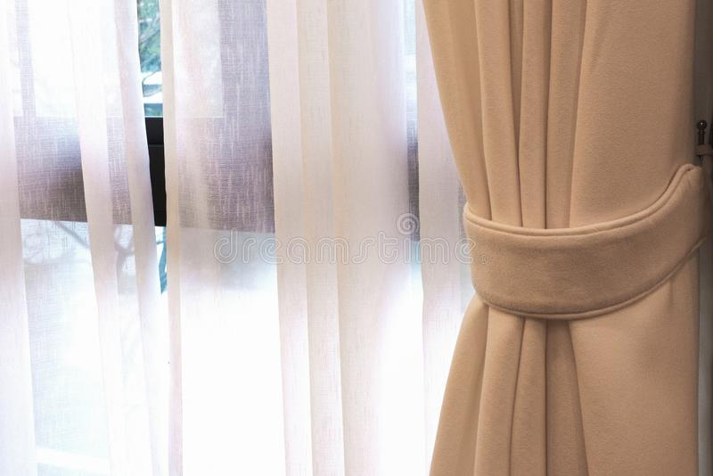 Beige gardin vid fönstret i sängmottaganderum arkivbilder