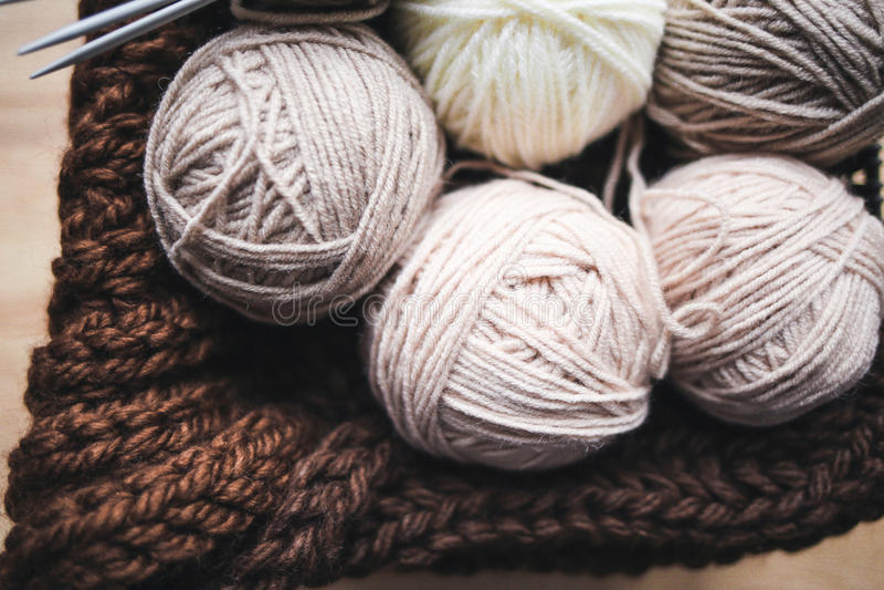 Beige Garn, Stricknadeln und ein brauner Schal sind im Korb lizenzfreies stockfoto