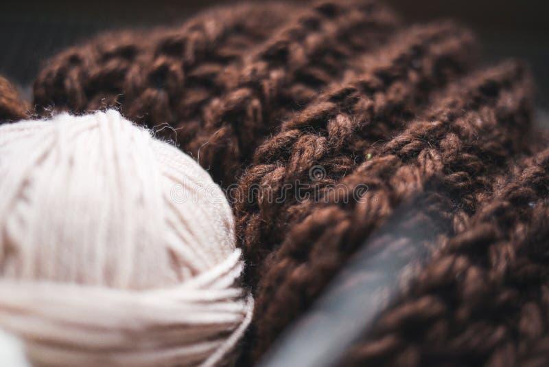 Beige Garn, Stricknadeln und ein brauner Schal sind im Korb stockfotografie