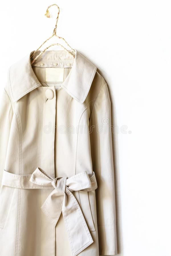 Beige of greige elegante trenchcoat met lint over wit stock fotografie