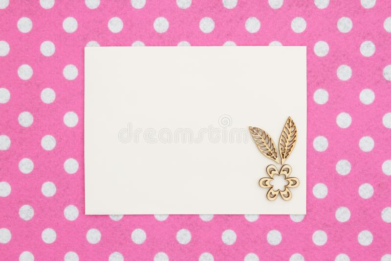 Beige Grußkarte des freien Raumes mit hölzerner Blume auf rosa und weißem Tupfengewebe stockfoto