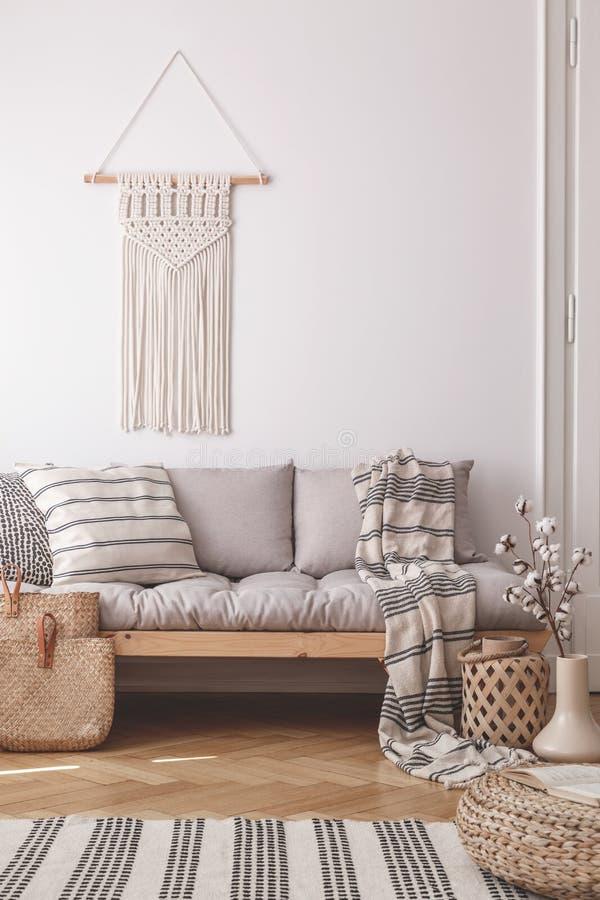 Beige, handgemachte Makramee auf einer weißen Wand über einer Couch mit einem gestreiften Leinenkissen in einem natürlichen Wohnz stockfotos