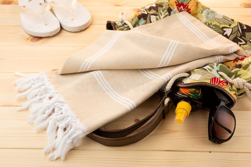 Beige handwoven hammam Turkish cotton towel on light wooden background. With colorful beach bag, flip flops, sunglasses and sun lotion beside stock photography