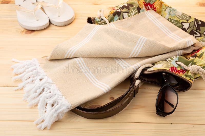 Beige Handwoven hammam Turkish cotton towel on light wooden background. With colourful beach bag underneath, flip flops and sunglasses beside stock image
