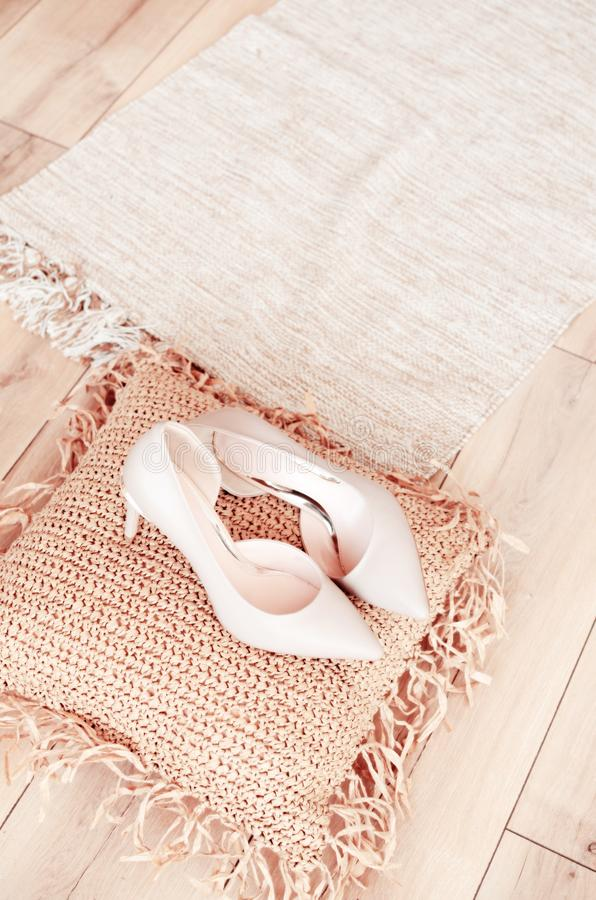 Beige high-heeled shoes elegant leather women`s shoes on a wooden background light glossy heel shoes on a pillow of. Straw royalty free stock images