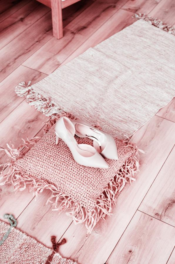 Beige high-heeled shoes elegant leather women`s shoes on a wooden background light glossy heel shoes on a pillow of. Straw stock images