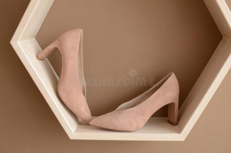 Beige high-heeled shoes elegant leather women`s shoes on a wooden background light glossy heel shoes. On a pillow of straw royalty free stock images