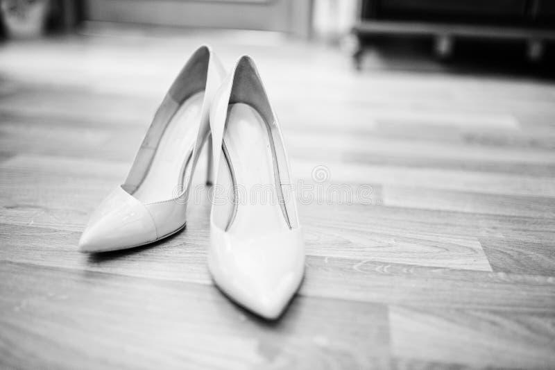 Beige huwelijksschoenen voor bruid op houten vloer Zwart-wit p royalty-vrije stock afbeelding