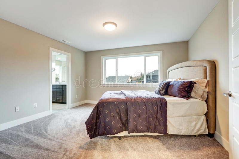 Beige ledar- sovrum med konungformatsäng royaltyfria bilder