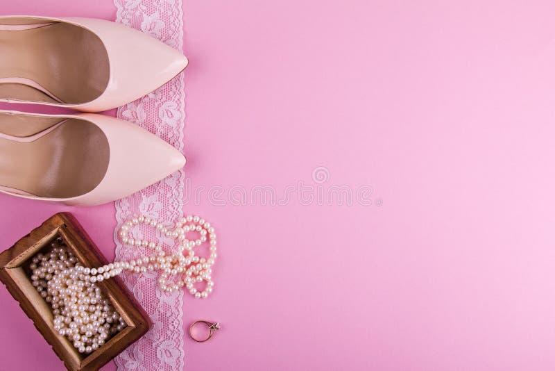 Beige leerschoenen met hoge hiel en toebehoren op roze achtergrond Plaats voor uw tekst Huwelijk, overeenkomst hen stock foto
