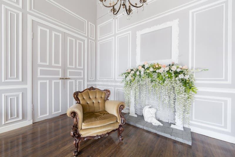 Beige leunstoel De decoratie van de de lentestijl De witte open haard Binnenland van heldere ruimte in klassieke koninklijke luxe stock afbeelding