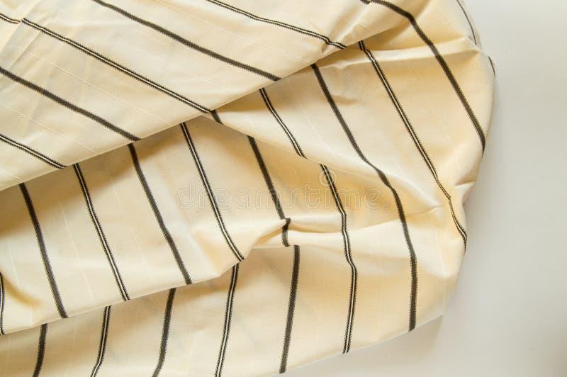 Beige linnetyg med svarta band, texturen av tyget royaltyfri foto