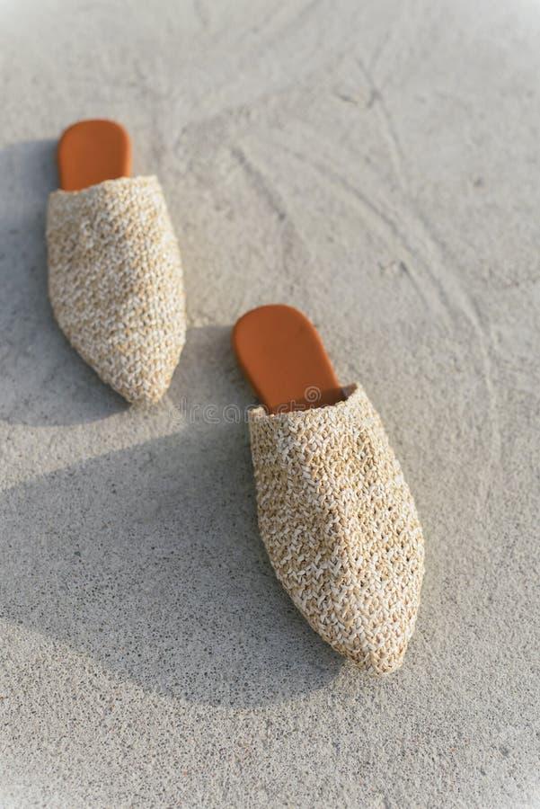 Beige manier rieten muilezels op de achtergrond van asfalt en beton modieuze, de zomer en tendensschoenen royalty-vrije stock afbeeldingen