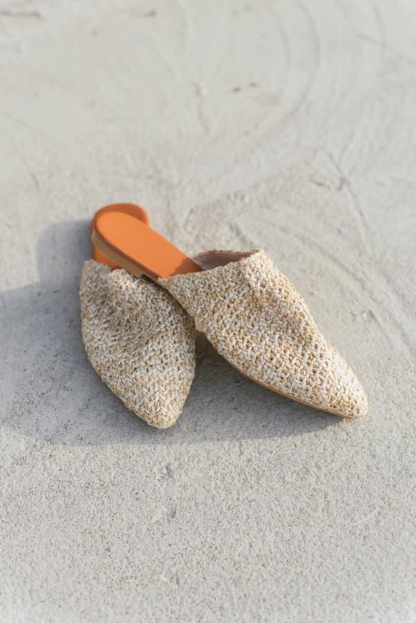 Beige manier rieten muilezels op de achtergrond van asfalt en beton modieuze, de zomer en tendensschoenen stock afbeelding