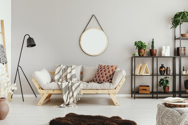 beige muur in modieuze bohowoonkamer met elegant bank en woedetapijt stock afbeeldingen