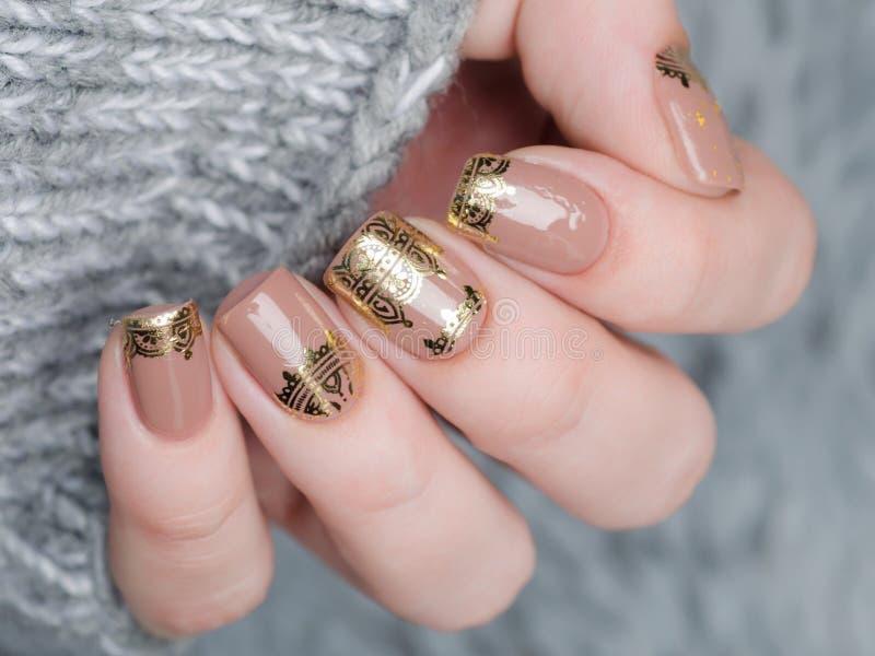 beige Nude manicure ze złotym koronkiem na szarym tle obrazy royalty free