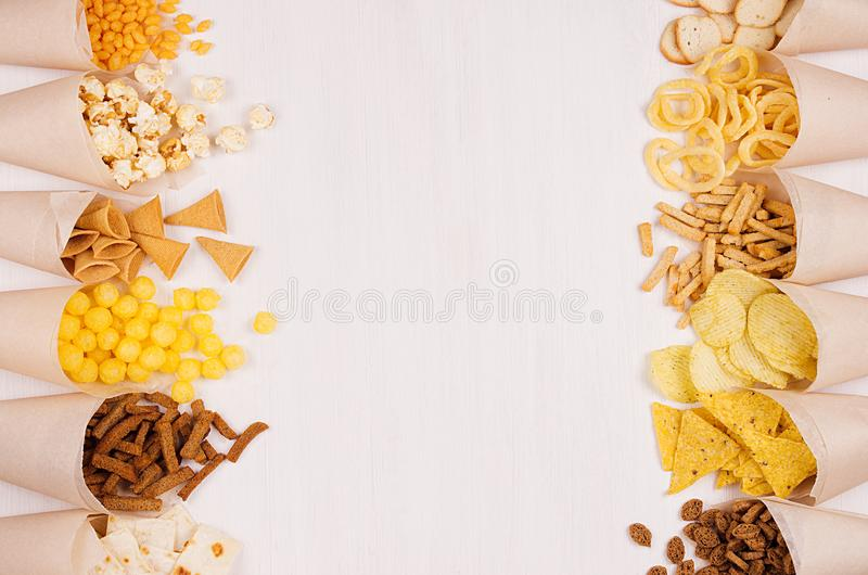 Beige paper cones with bright crunchy fast food snacks - nachos, popcorn, croutons, chips on white wood board, copy space. Beige paper cones with bright crunchy stock photos