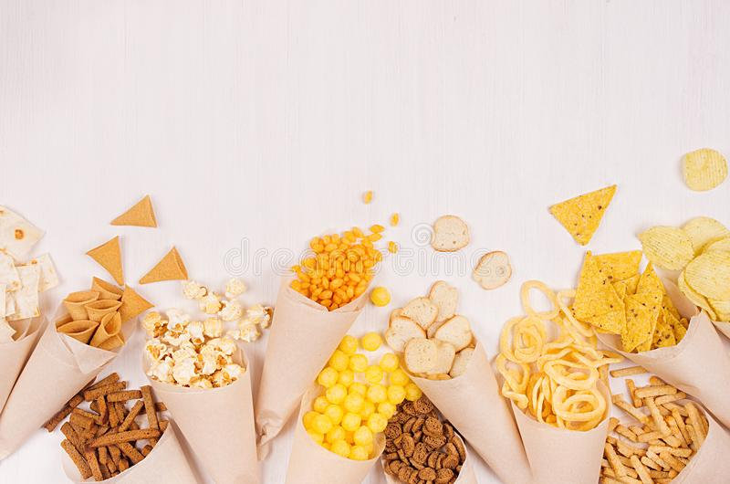 Beige paper cones with bright crunchy fast food snacks - nachos, popcorn, croutons, chips on white wood board, copy space. Beige paper cones with bright crunchy stock image